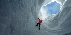 Man climbing glacier with ice pick